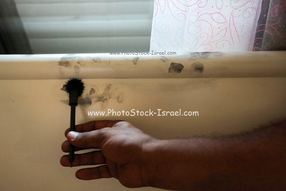 Crime scene investigator is looking for fingerprints after a burglary that happened the previous night through the nursery's window. Photographed in Israel
