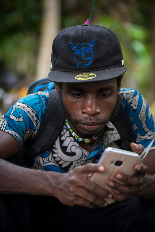 A man looks at his mobile phone in a village on the Ramu River in Madang Province, Papua New Guinea.