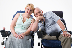 Disabled couple leaning together and smiling,