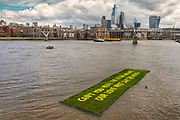 'Can't you hear the future weeping? Our love must save the world', a statement by writer Ben Okri was revealed in a live art piece by eco Artists Ackroyd & Harvey on 25th July 2021 floating in the Thames in front of Tate Modern, London, United Kingdom. Conceived as a message to us all, the artists were calling yet again for us to act in the face of our climate crisis. In the temporary 'greenhouse' of Tate, the seeds burst into life with the added dimension of Okri's clarion call to use active love to inspire the change we need. Stencilled letters, blocking the light, then removed, created the message within the grass. For the final act, in a solemn ritual, the grass banner was rolled up, carried out by volunteer performers and floated on the Thames. Visible from up high, floating on the tidal river, the luminescent yellow letters stood out boldly from the rich green of the grass. At the end of the day the banner was dismantled and the grass art distributed to anyone who wanted to continue to grow the words.