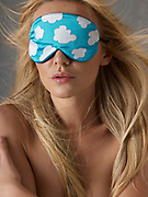 Close up of woman's face wearing a sleeping mask with cloud pattern over eyes