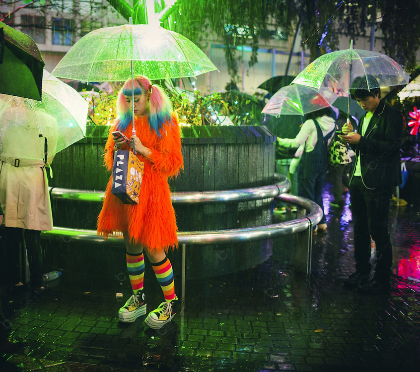 Woman dressed in cosplay style using her smartphone under the rain at night in Shibuya Tokyo Japan. Shibuya is one of the 23 special wards of Tokyo. With 15 square kilometer and a resident population of more than 200000 people it has become one of the best shopping districts of the city specially for young people. It has also a lively nightlife and the streets are busy until late at night.
