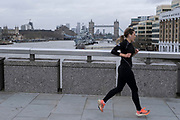 Woman running across London Bridge looking towards Tower Bridge as the national coronavirus lockdown three continues on 28th January 2021 in London, United Kingdom. Following the surge in cases over the Winter including a new UK variant of Covid-19, this nationwide lockdown advises all citizens to follow the message to stay at home, protect the NHS and save lives.