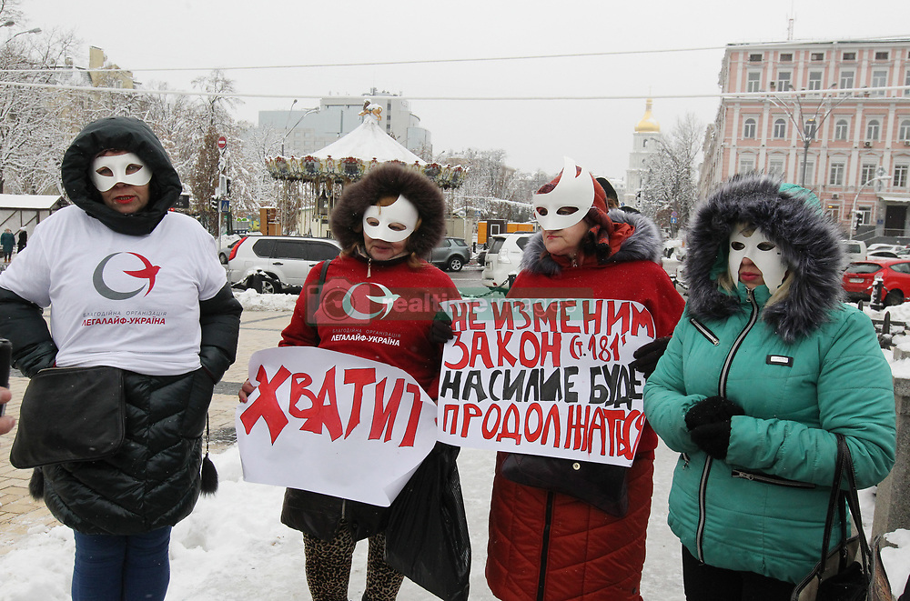 December 17, 2018 - Kiev, Ukraine - Activists and former sex workers wearing white masks hold banners reading: ''If do not change a law, the violent will go on!'' and ''Enough'' during a protest against violence and cruelty towards sex workers in downtown Kiev. The protest timed to the International Day to End Violence Against Sex Workers, which is mark annually on 17 December in the world. (Credit Image: © Pavlo Gonchar/SOPA Images via ZUMA Wire)