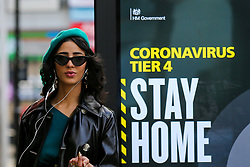 © Licensed to London News Pictures. 25/12/2020. London, UK. A woman poses next to the government's 'Stay Home- Tier 4' publicity campaign poster in north London amid fears of a third national lockdown after Christmas as COVID-19 infection rates rise. Many more areas of England will go into Tier 4 restrictions from Boxing Day as the mutated strains continue to spread throughout England. Photo credit: Dinendra Haria/LNP