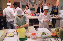 Men and women with learning disabilities helping prepare food in kitchen,