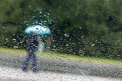 THEMENBILD - ein Spaziergänger mit Regenschirm, durch eine mit Regentropfen benetzte Scheibe eines PKWs fotografiert, aufgenommen am 12.08.2014 in Kaprun, Österreich // a Women carrying an umbrella, photographed from behind a window, covered with rain drops during rainy weather in Kaprun, Austria on 2014/08/12. EXPA Pictures © 2014, PhotoCredit: EXPA/ JFK
