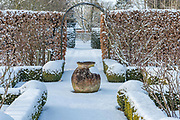 The Potager with Buxus - box hedging and topiary shapes. Fagus - Beech hedge and  terracotta oil jar with a covering of snow in late February. The Old Rectory, Brinkley - 'Shapely, low-level box edging frames the borders in the veg garden, while beech and yew hedges at a higher level contain the wild garden. The view through the arches and openings in the hedges leads to a woven willow fence that backs a new border near the house.' B Seagall