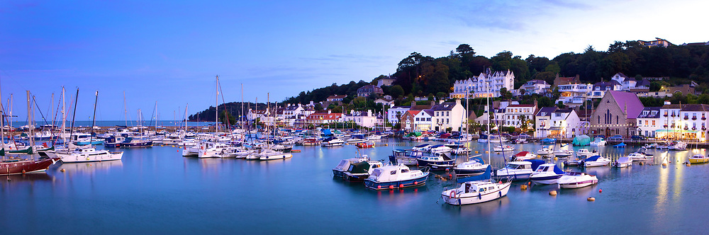 Boats and yachts moored up in the calm water of St Aubin's bay harbour at dusk, in Jersey, Channel Islands