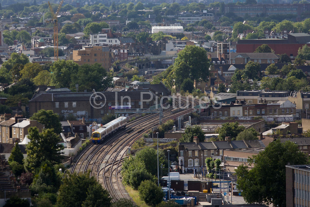 An aerial view of south London looking from Camberwell towards a commuter train crossing the capital. Transport by rail can ben seen clearly as we look down on to this landscape of urban sprawl in south London: The railway tracks zig-zag through the heart of the borough of Lambeth, near Loughborough Junction, Brixton - showing us how in the late-1800s, the city was sliced through by such rail routes that helped open up the city to the less wealthy - adding to the inner-city. This route is known as the London Bridge (in the east) to Victoria (west)  loop that provides a shortcut across the southern regions, from one station to another.