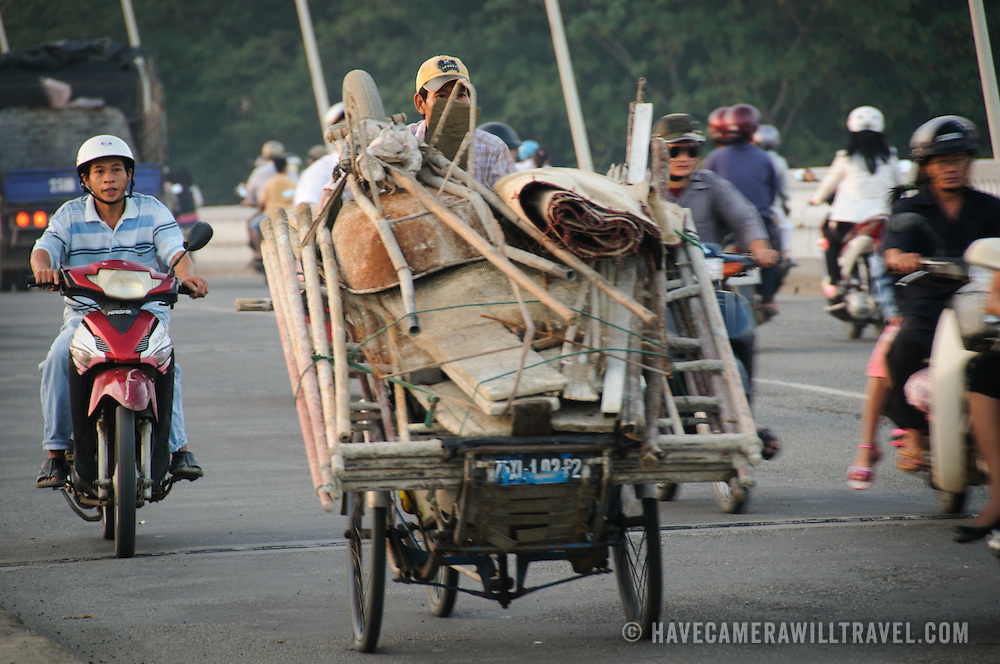A construction worker transports his equipment across Cau Phu Xuan in the evening in Hue, Vietnam.