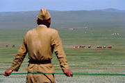 Khui Doloon Khudag, Mongolia, July 2003..Competitors & spectators at the horse racing in the national Naadam 40 kilometres outside Ulaanbaatar..Mongolian soldiers line the race track across the steppes.