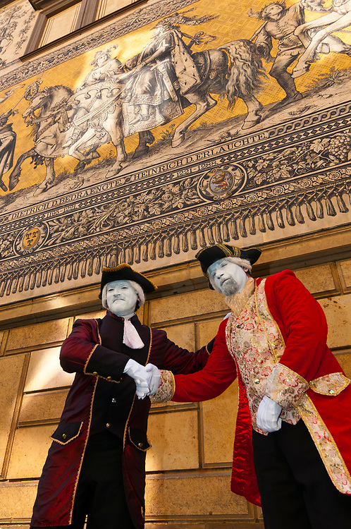 Mimes in historical costume with the 100 meter long Procession of Princes (the largest porcelain image in the world, made up of 25,000 tiles) in the background. It shows a total of 35 princes, dukes, margraves and kings on horseback and 59 scientists, artisans, craftsmen and farmers) from the House of Wetten (rulers of Saxony from 1127-1918), Augustusstrasse, Dresden, Saxony, Germany