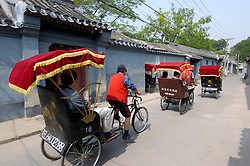 Tourists traveling along Beijing hutong by rickshaws on guided tour