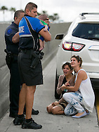 Sweetwater officer Amauris Bastidas helps rescue a five-month-old baby boy, Sebastian de la Cruz,  who stopped breathing. At center, the baby's aunt, Pamela Rauseo, 37, performed CPR after pulling her SUV over on the side of the road along the west bound lane on Florida state road 836 just east of 57th Avenue around 2:30pm on Thursday, February 20, 2014.  At right is Lucila Godoy who stopped her car to assist in the rescue.
