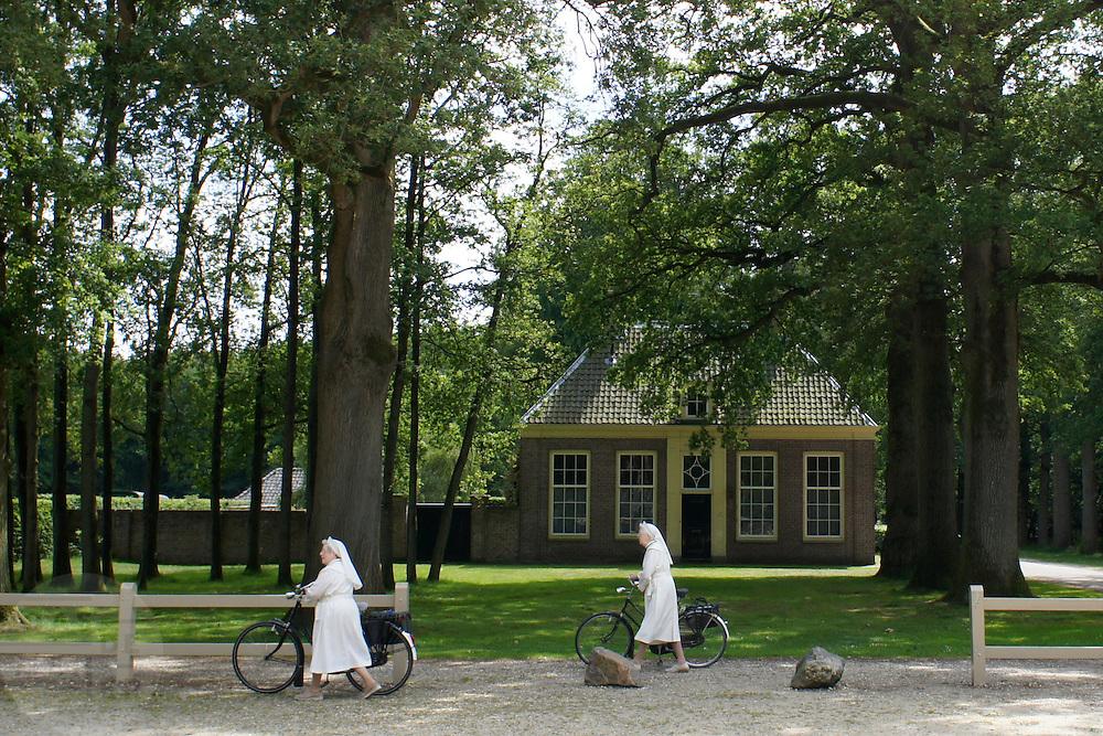 Twee zusters lopen met de fiets bij Kasteel Groeneveld in Baarn