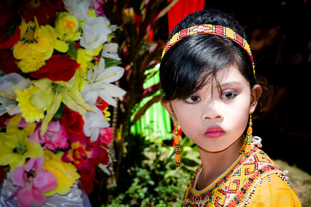 Indonesia, Sulawesi, Tana Toraja. The Torajan girl wearing a traditional outfit.<br /> <br /> Tana Toraja, situated in the south of Sulawesi, sometimes reminds alive museum full of traditional boat-shaped houses painted with Torajan patterns, burial caves or hanging graves guarded by tau tau (a deceased shaped wooden sculptures(, all of them situated in a beautiful scenery of green rice terraces.