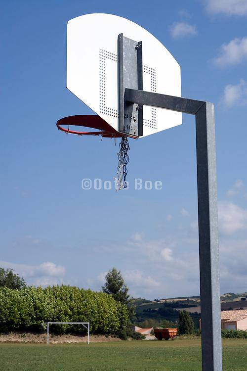 basketball hoop with broken net in a rural setting