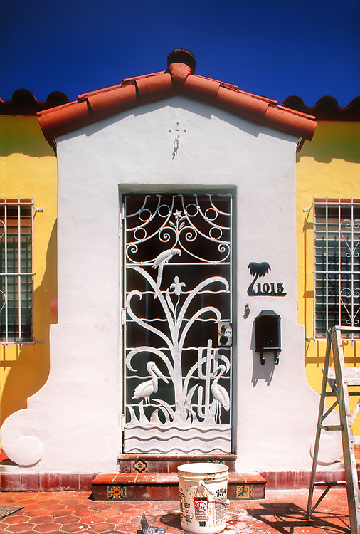 A vintage Art Deco screen door getting a paint job in Miami Beach. This small private home in the Fl;amingo Park neighborhood  features such Florida motifs as waves, tropical birds, and palm trees. And a cactus, which grows in Florida. is also depicted. Florda.