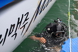 A diver surfaces with a knife after cutting rope from the propellor of one of the yachts. Korea Match Cup 2010. World match Racing Tour. Gyeonggi, Korea. 12 June 2010. Photo: Gareth Cooke/Subzero Images