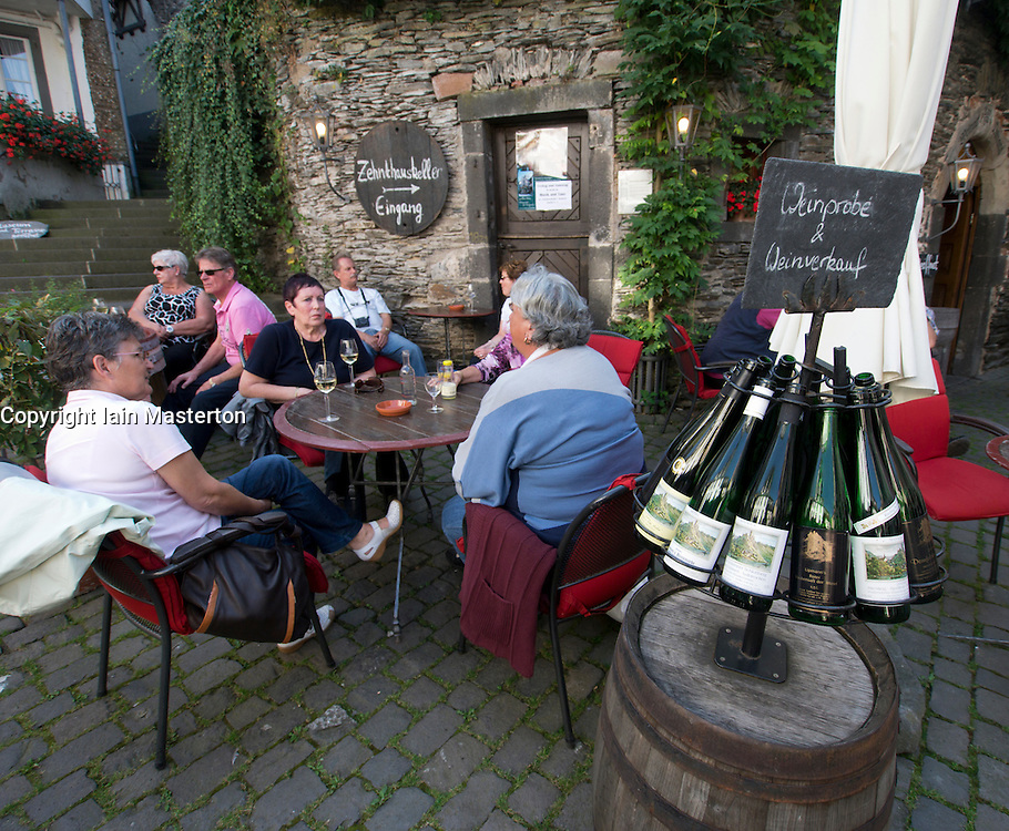 Tourists drinking wine in square in historic village of Beilstain in Mosel Valley Rhineland Germany