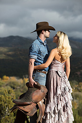 cowboy and beautiful woman with blonde hair and long antique dress overlooking a mountain