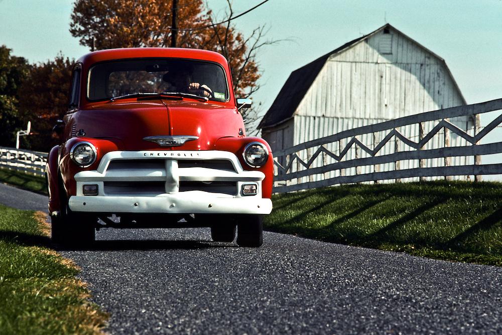 A classic Chevy Truck driving through a farm.