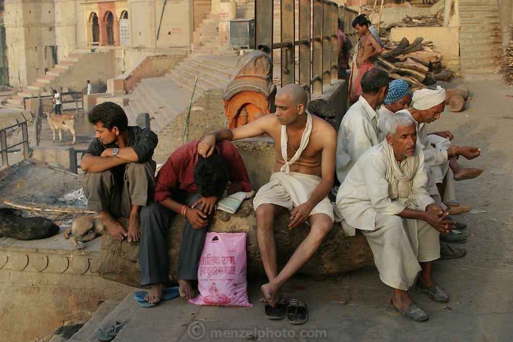 Mourners comfort each other at the cremation grounds at Manikarnika Ghat. One hundred or more times a day male family members carry a loved one's body through the narrow streets on a bamboo litter to the Ganges River shore, a place of pilgrimage for Hindus during life, and at death.