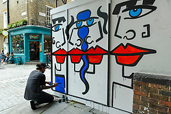 "© Licensed to London News Pictures. 04/08/2020. LONDON, UK.  An assistant to artist Anna Laurini works on her new artwork ""Urban Spinxes"".  Located outside a construction site just off Carnaby Street, the piece is  inspired by Pablo Picasso and Henri Matisse.  The construction company commissioned the artist to design something to cover up what would otherwise be bare wooden hoardings.  Photo credit: Stephen Chung/LNP"