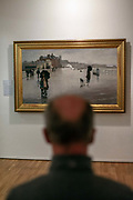 A man looks at a painting by the Newlyn School at the Penlee House Gallery, Penzance, United Kingdom.