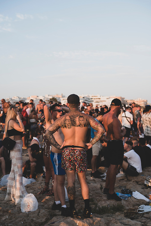 Sant Antoni de Portmany, Ibiza, Spain - August 3, 2018:  A large crowd of mostly young adults gathers for sunset at the beach on the 'sunset strip' in San Antonio, Ibiza.