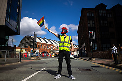 """© Licensed to London News Pictures . 28/08/2021. Manchester, UK. A traffic marshal stops traffic to allow the protest to pass along the road . People take part in a Reclaim Pride march through Manchester City Centre , in opposition to the management of the city's """"official"""" Manchester Pride charity festival . The Manchester Pride charity parade was cancelled in 2020 due to Coronavirus . An """"equality march"""" organised by Manchester Pride charity was due to take place on Deansgate as the protest passed through the Gay Village . Protesters object to Manchester Pride charity's withdrawal of funding for the LGBT Foundation's condom distribution scheme and HIV charity George House Trust as well as increasing commercialisation of the annual event . Photo credit: Joel Goodman/LNP"""