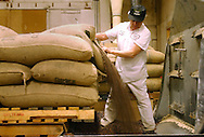 Antonio Solano rips open a bag full of coca beans and pours it into a hopper, that leads to the roasting process at the Guittard Chocolate Factory in Burlingame, Calif. on Thursday Jan. 31, 2002. Solano has been with Guittard for 41 years.(Photo by Jakub Mosur)