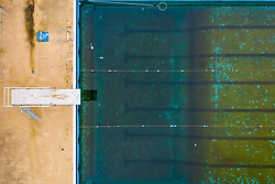 Gourock, Scotland, UK. 9 Mar 2021. Coronavirus lockdown has meant Gourock outdoor swimming pool has been closed to the public for months and the water in the pool has become stagnant and dirty. Much maintenance and cleaning will be required to bring the pool to readiness when lockdown is relaxed.  Pic; Aerial view looking down onto pool and diving board.  Iain Masterton/Alamy Live News