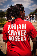 Back of a T-Shirt saying 'Chávez doesn't go' during the funeral of the President of Venezuela in Caracas, 8th March, 2013. During Hugo Chávez funeral many people and stand sold miscellaneous articles that perpetuate Chávez presence. Everything from T-shirts, badges, earrings, baseball caps, sun glasses seemed suitable to have the President's image. The cult of Chávez is now more alive than ever.