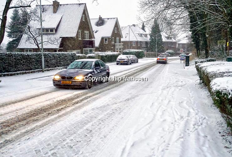 Nederland, Ubbergen, 22-1-2019 De eerste sneeuw van deze winter is gevallen. Bij de Elysese velden . Auto rijdt voorzichtig over de besneeuwde weg,straat . autoverkeer,autos .Foto: Flip Franssen