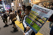 A tout holds a sign showing the World cup soccer games of the Japan National Team in Center Gai, Shibuya Tokyo. Japan Thursday June 28th 2018. Japan lost to Poland  0-1 but managed to move to the next stage on points. Thousands of younger fans gathered at Tokyo's iconic Shibuya crossing to enjoy the moment with police controlling the crowds