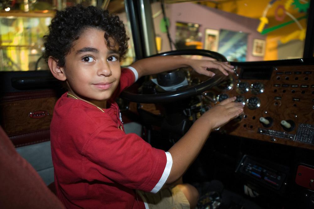 United States, Washington, Bellevue, KidsQuest Children's Museum, boy driving giant truck