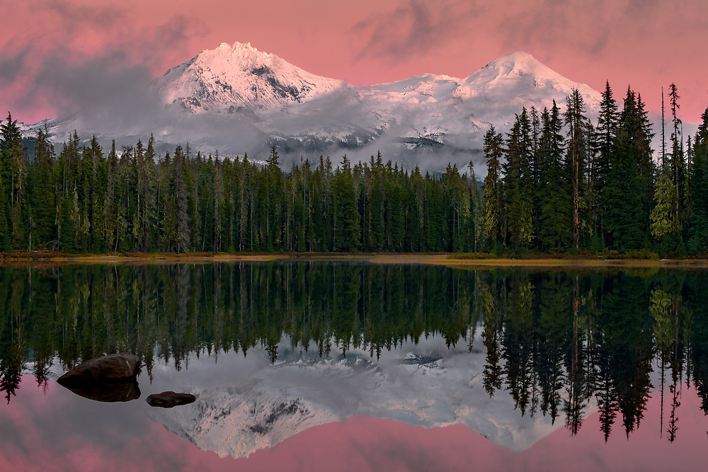 A sunset alpenglow warms a fresh autumn snowfall on North and Middle Sisters peaks, as seen from Scott Lake, in the Oregon Cascades.