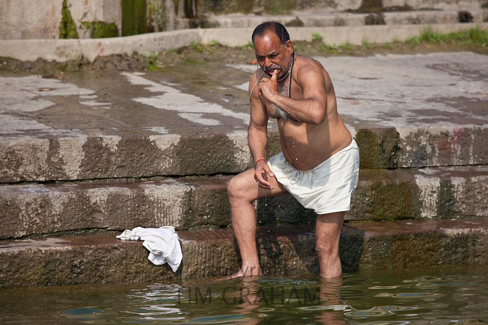Indian Hindu man bathing and cleaning his teeth in the River Ganges by Kshameshwar Ghat in holy city of Varanasi, India