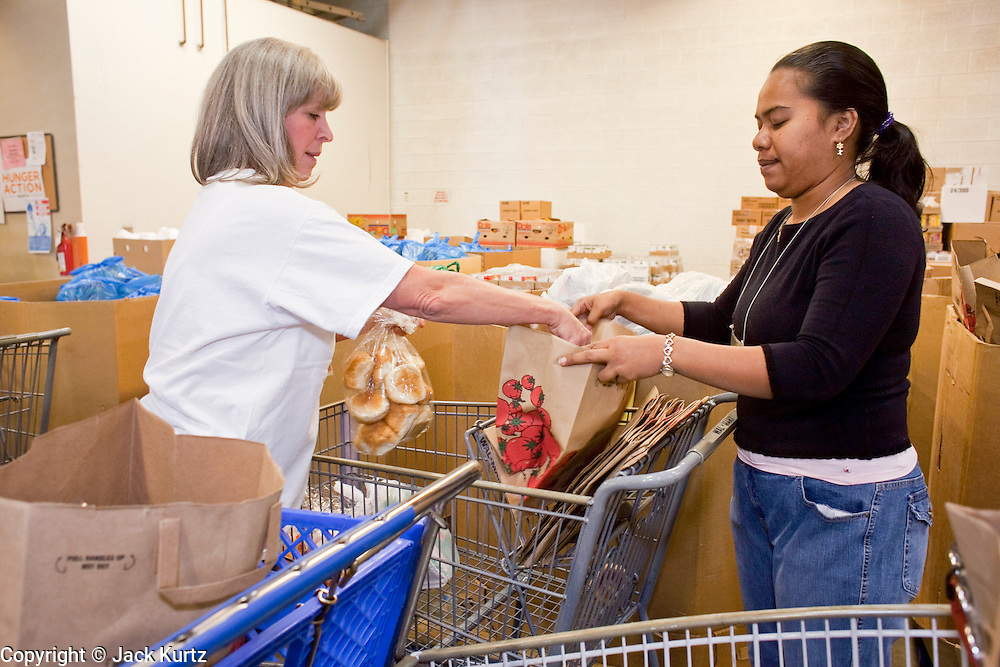 Apr. 3, 2009 -- MESA, AZ: LAURA QUIGLEY, left, and YOSKO HARBER, volunteers at the United Food Bank, fill shopping carts for clients. A spokesperson for the United Food Bank in Mesa, AZ, said demand has increased by more than 100 percent in the last year. She said that at this time in 2008, about 175 people a week (the food bank is open one day a week) bought 200 boxes a food but now they were seeing about 350 people per week and they were buying 400-450 boxes of food per week. Each box of food cost $16 and contains enough food for five meals for two people, including meat, fruit and vegetables and starches. In addition to the food boxes, the food bank gives away perishables, like fresh baked goods and produce, that are donated by Phoenix area grocery stores and food producers. She said the number of donations to the food bank have increased as the economy has worsened but each donation is smaller and the gap between donations and what the food bank needs is widening.    Photo by Jack Kurtz / ZUMA Press
