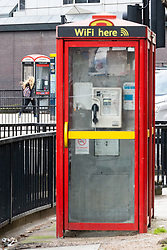 Two older style phoneboxes, one a double, are on either side of the road as modern public telephones carrying illuminated advertising add to the clutter of signs, lampposts, sandwich boards, bus shelters and street furniture on Edgeware Road in London. LONDON, February 12 2019.