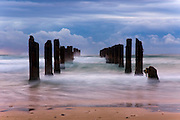 Israel, Beit Yanai, Poles in the sea the remains of a wharf long exposure,