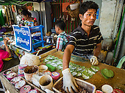 "06 NOVEMBER 2015 - YANGON, MYANMAR: A vendor makes betel nut in his Yangon stand. Some economists think Myanmar's informal economy is larger than the formal economy. Many people are self employed in cash only businesses like street food, occasional labor and day work, selling betel, or working out of portable street stalls, doing things like luggage repair. Despite reforms in Myanmar and the expansion of the economy, most people live on the informal economy. During a press conference this week, Burmese opposition leader Aung San Suu Kyi said, ""a great majority of our people remain as poor as ever.""  PHOTO BY JACK KURTZ"
