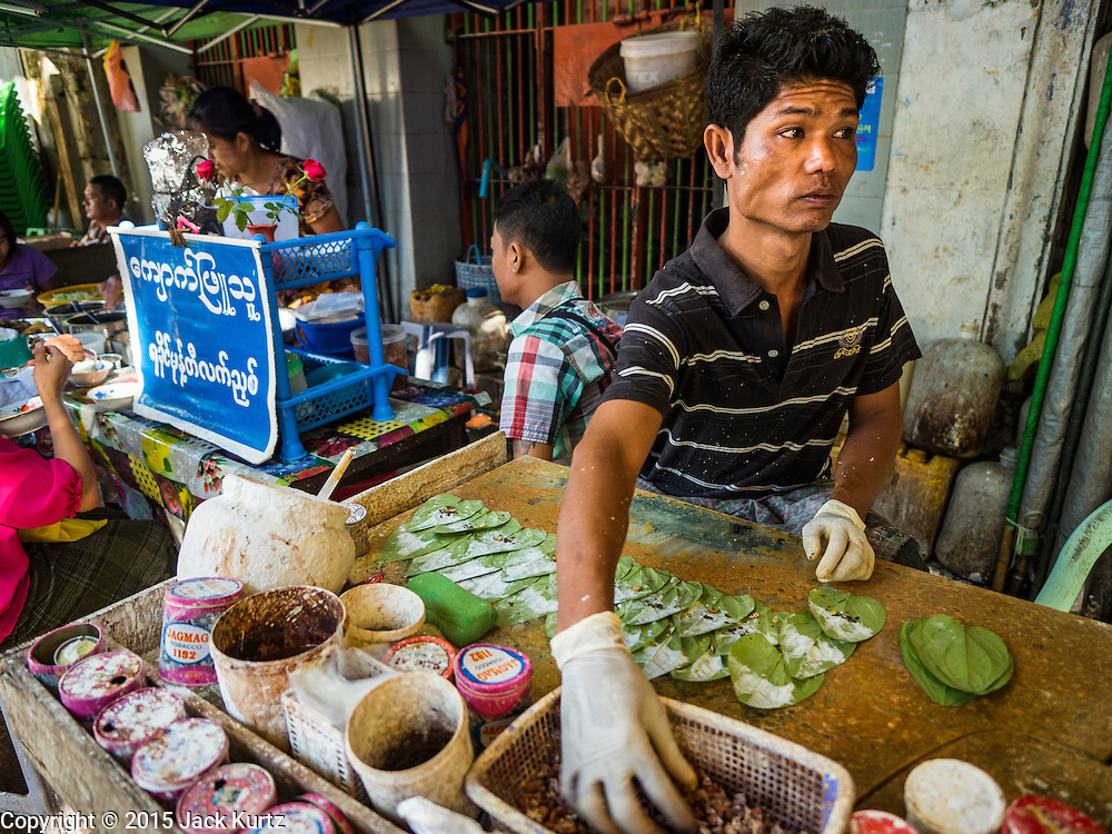 """06 NOVEMBER 2015 - YANGON, MYANMAR: A vendor makes betel nut in his Yangon stand. Some economists think Myanmar's informal economy is larger than the formal economy. Many people are self employed in cash only businesses like street food, occasional labor and day work, selling betel, or working out of portable street stalls, doing things like luggage repair. Despite reforms in Myanmar and the expansion of the economy, most people live on the informal economy. During a press conference this week, Burmese opposition leader Aung San Suu Kyi said, """"a great majority of our people remain as poor as ever.""""  PHOTO BY JACK KURTZ"""