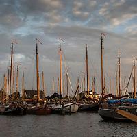 Haven in Heeg. Masten verlicht door de ondergaande zon