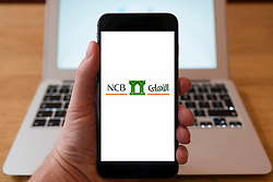 Using iPhone smart phone to display website logo of NCB Bank National Commercial Bank of Saudi Arabia