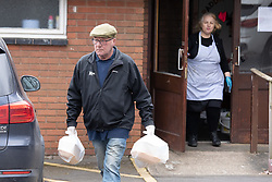 © Licensed to London News Pictures. 30/03/2020. Baddesley, North Warwickshire, UK. MP Delivery. Pictured a volunteer watched by Angie Spencer. North Warwickshire MP Craig Tracey turns delivery man to help deliver meals in his constituency. When Atherstone coffee shop owner Angie Spencer decided to make meals for people who were housebound she asked for volunteers to help deliver the meals. The local community responded along with local MP Craig Tracey. The meals will be delivered on Mondays and Fridays to start with, the first going out today (Monday 30th March) with over 100 meals being delivered. Angie has put out a request for more drivers should the need rise. Angie, a local town councillor started the idea along with business partner Stephen Reay and asked Warwickshire County Council to help with the scheme. Photo credit: Dave Warren / LNP