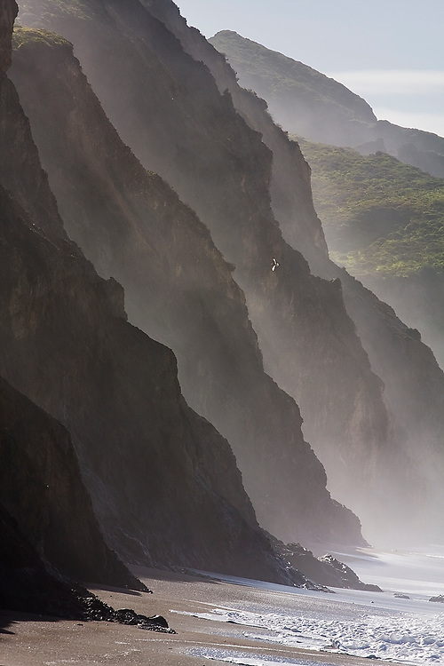 A series of steep cliff ridges in heavy mist along Wildcat Beach, Point Reyes National Seashore, California. The beach can only be hiked at low tide as waves come crashing into the cliffs at high tide.