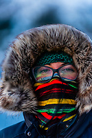 A woman wearing a balaclava and cold weather gear standing on the deck of the Hurtigruten ship MS Vesteralen in winter, sailing between Alesund and Molde, Norway.